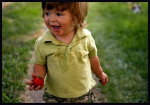 Kids should garden because it gives them exercise, as this little boy with the tomato shows.