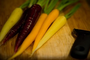 orange and purple carrots on a cutting board