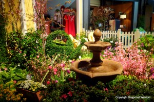 spring flowers and three-level fountain in romantic-style garden