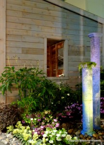 water columns that serve as fountains in beach-style garden