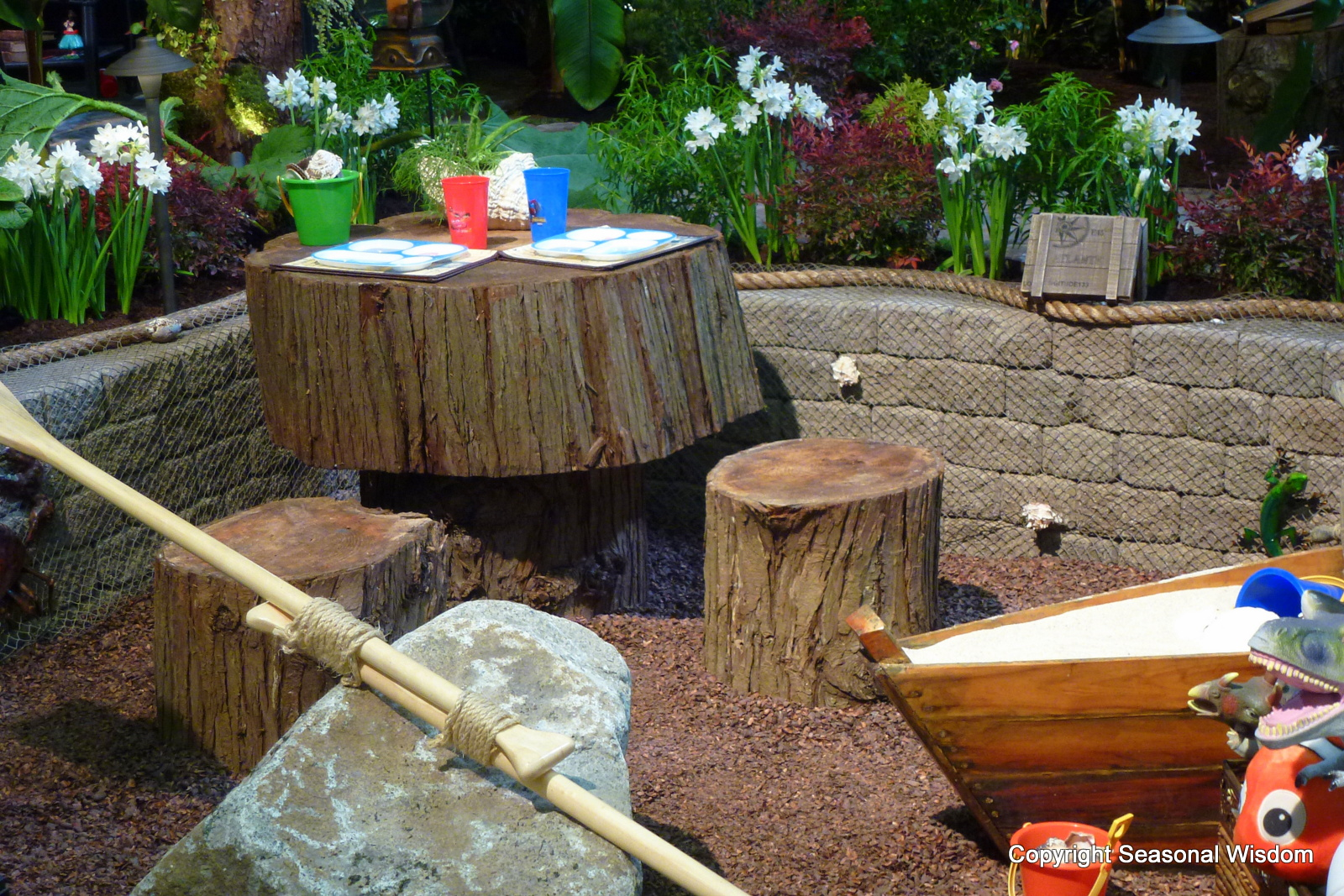 close up of kids garden with wooden table teeter totter and sandbox - Sandbox Design Ideas