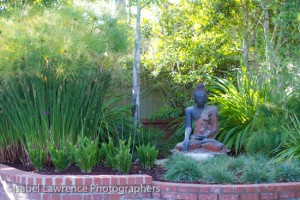 A four-foot Buddha in garden designed by Billy Goodnick.