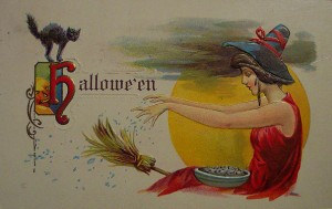A witch flies on a broom in this vintage Halloween card