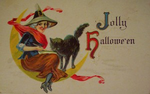 A witch flies on a moon in this vintage Halloween card