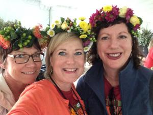 Three women wear flower wreaths at field to vase dinner with american grown flowers